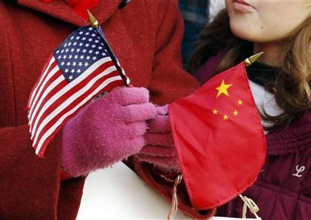 A girl holds a U.S. and Chinese flag as she waits for U.S. President Barack Obama to welcome Chinese President Hu Jintao during an official south lawn arrival ceremony at the White House in Washington January 19, 2011. REUTERS/Kevin Lamarque/Files