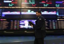 Трейдер проходит мимо экранов на Нью-Йоркской фондовой бирже, 18 января 2011 года. Рынки США разнонаправлены в начале торгов. REUTERS/Brendan McDermid