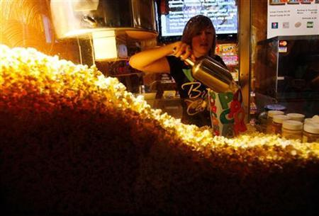 Cailynn Williams, 17, fills a bag of popcorn for a customer at the New Strand Theater in West Liberty, Iowa July 8, 2011. Todd Leach, who owns the New Strand Theater, says that ticket sales are down from last summer due to the economy. Voters in the Iowa caucus and the New Hampshire primary will be the first to cast ballots in the upcoming U.S. Presidential race. REUTERS/Jessica Rinaldi