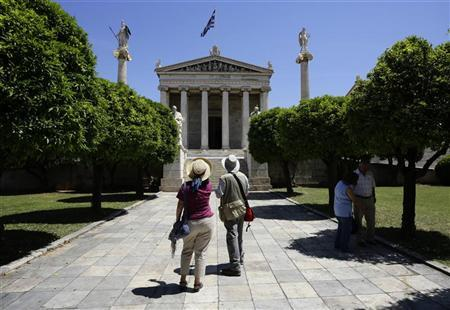 Tourists look at the Athens Academy May 7, 2012. REUTERS/Kevin Coombs