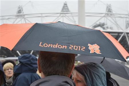 A spectator shelters under an umbrella with a London 2012 Olympics logo in the Olympic Park at Stratford, east London May 3, 2012. REUTERS/Toby Melville