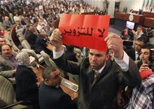 <p>نائب عن تحالف الجزائر الخضراء الاسلامي يرفع لافتة كتب عليها (لا للتزوير) في الجلسة الافتتاحية للبرلمان الجزائري يوم السبت - رويترز</p>