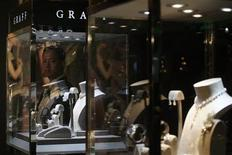 A suited bodyguard stands next to a jewellery display window during the Graff Diamonds IPO roadshow in Hong Kong May 21, 2012. Luxury jeweler Graff Diamonds, famous for its giant and rare gems, is forging ahead with a Hong Kong listing despite a sell-off that has rattled equity markets, setting a price range on Friday that would value the company at up to $4 billion. REUTERS/Tyrone Siu