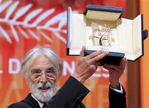 "Director Michael Haneke reacts after receiving the Palme d'Or award for the film ""Amour"" (Love) during the awards ceremony of the 65th Cannes Film Festival, May 27, 2012. REUTERS/Yves Herman"