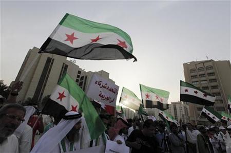 5月27日、国連安保理は、シリア西部ホムス近郊の町ホウラで100人以上が死亡した大規模な砲撃を受けて緊急会合を開き、攻撃を非難する声明を承認した。写真はシリアのアサド政権に抗議するデモ。バーレーンで撮影(2012年 ロイター/Hamad I Mohammed)