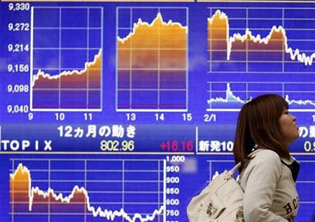 A woman smiles as she walks past an electronic board displaying graphs showing recent movements of Japanese market indices, outside a brokerage in Tokyo February 15, 2012. REUTERS/Yuriko Nakao