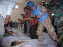Наблюдатель ООН фотографирует тела погибших детей в сирийском городе Эль-Хула 26 мая 2012 года. Совет безопасности ООН в воскресенье единогласно осудил гибель 108 сирийцев, в том числе многих детей, при обстреле города Эль-Хула, вину за который власти страны и повстанцы сваливают друг на друга. REUTERS/Shaam News Network/Handout