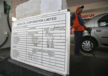 A worker fills a car with petrol next to a price tag board installed at a fuel station in Noida, on the outskirts of New Delhi May 24, 2012. REUTERS/Parivartan Sharma