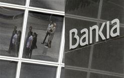 Пешеходы отражаются в здании головного офиса Bankia в Мадриде 26 мая 2012 года. Испания может рекапитализировать Bankia посредством гособлигаций в обмен на акции банка, запросившего на прошлой неделе финансовую помощь в размере 19 миллиардов евро ($24 миллиарда), сообщил Рейтер источник, близкий к правительству. REUTERS/Andrea Comas