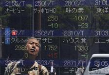 Мужчина смотрит на экран с фондовыми котировками возле брокерской конторы в Токио 10 мая 2012 года. Азиатские фондовые рынки выросли в понедельник, причем для Японии это стало первым подъемом после восьминедельного спада. REUTERS/Toru Hanai
