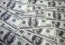 Купюры номиналом 100 долларов США в банке в Сеуле 20 сентября 2011 года. Консорциум иностранных компаний во главе с итальянской Eni и американской Exxon Mobil оплатит двухлетнюю долю инвестиций госхолдинга Казмунайгаз на сумму около $1 миллиарда в проект разработки крупнейшего казахстанского нефтегазового месторождения Кашаган. REUTERS/Lee Jae-Won