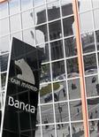 Улица Мадрида отражается в здании головного офиса банка Bankia 26 мая 2012 года. Испания может рекапитализировать Bankia посредством гособлигаций в обмен на акции банка, запросившего на прошлой неделе финансовую помощь в размере 19 миллиардов евро ($24 миллиарда), сообщил Рейтер источник, близкий к правительству. REUTERS/Andrea Comas