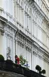 Женщина ухаживает за растениями на балконе дома в Лондоне, 30 августа 2011 г. Увядающие и изнемогающие от жажды комнатные растения могут рассчитывать на большую нежность и уход благодаря новому сенсору и приложению, информирующим хозяев о том, когда пришло время полива и подкормки. REUTERS/Luke MacGregor