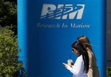 One of the women uses a mobile phone as they walk at the Blackberry maker's Research in Motion RIM campus in Waterloo April 18, 2012. Picture taken April 18, 2012. REUTERS/Mark Blinch