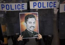 A protester holds a picture of Bahraini human rights activist Abdulhadi al-Khawaja in front of riot police during an anti-government rally demanding his release, in Manama in this April 18, 2012 file photo. REUTERS/Ahmed Jadallah/Files