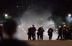 Montreal police stand in front of smoke from an unknown source, during a protest against student tuition hikes on the 100th day of Quebec's student strikes, in downtown Montreal May 22, 2012. REUTERS/Brett Gundlock