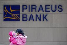 Женщина с ребенком проходит мимо отделения греческого Piraeus Bank в Бухаресте 18 февраля 2009 года. Греция выделила 18 миллиардов евро ($22,6 миллиарда) четырем крупнейшим банкам, чтобы вновь открыть им доступ к кредитованию Европейского Центробанка (ЕЦБ), сообщило министерство финансов Греции. REUTERS/Bogdan Cristel