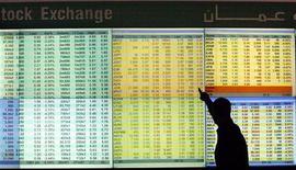 Брокер смотрит на рыночные котировки на Амманской фондовой бирже 3 мая 2010 года. Низкая активность компаний из России на рынке первичных размещений может обернуться распродажей активов по невыгодным ценам в случае снижения цен на нефть, считает старший аналитик Альфа-банка Ангелика Генкель. REUTERS/Ali Jarekji