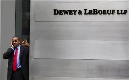 A man talks on his phone behind the sign, outside of the building housing the law firm Dewey & LeBoeuf LLP in New York, May 8, 2012. REUTERS/Lucas Jackson