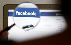 Женщина разглядывает логотип Facebook через увеличительное стекло в Берне 19 мая 2012 года. Сделка по покупке Opera Software может стоить Facebook более $1 миллиарда из-за конкуренции со стороны Google и других претендентов на покупку норвежского разработчика программного обеспечения. REUTERS/Thomas Hodel