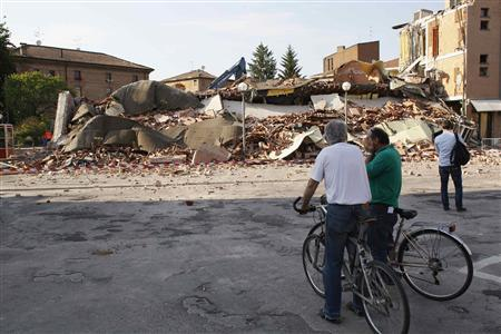 People stand in front of a damaged building in Cavezzo near Modena May 29, 2012. An earthquake killed at least 15 people in northern Italy on Tuesday, damaging buildings and spreading fear among thousands of residents living in tents after a similarly strong tremor in the same region flattened their homes nine days ago. REUTERS/Stefano Rellandini