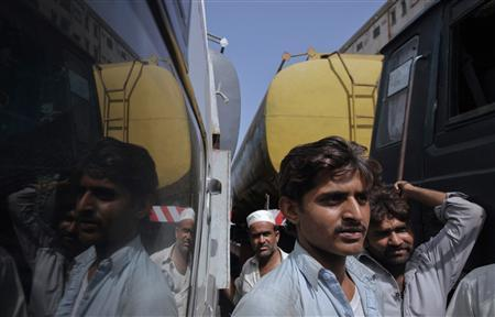 Riyasat Ali (2nd R), 21, along with other drivers are reflected in a window of a fuel tanker, which was used to carry fuel for NATO forces in Afghanistan, parked at a compound in Karachi May 24, 2012. REUTERS/Akhtar Soomro