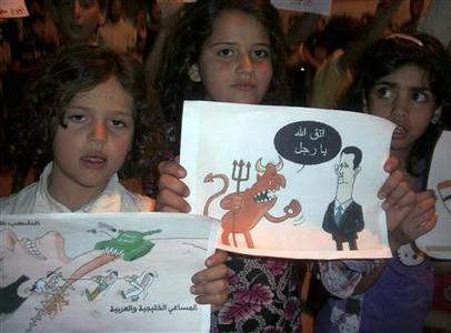 Syrian children hold up signs during a night demonstration at Sarmada on the outskirts of Idlib May 29, 2012. REUTERS/Stringer