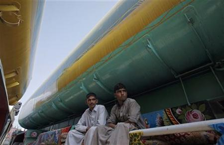 Malik Abdul Rauf (L), a 23-year-old driver, and Karamatullah, a 20-year-old cleaner, sit at a fuel tanker, which was used to carry fuel for NATO forces in Afghanistan, parked at a compound in Karachi May 24, 2012. REUTERS/Akhtar Soomro