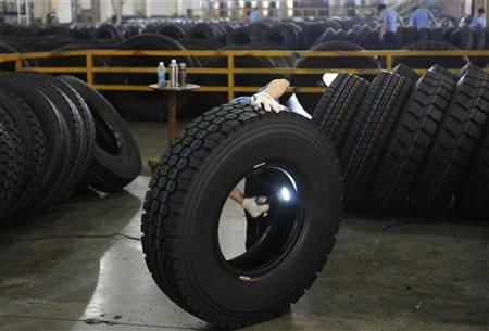An employee inspects the interior of a newly-made tyre with a flashlight at a tyre factory in Hangzhou, Zhejiang province May 29, 2012. REUTERS/Lang Lang