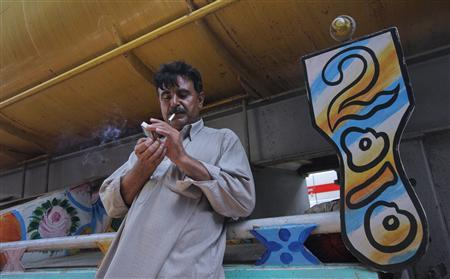 Saifur Rehman, a 47-year-old driver, lights up a cigarette while standing beside a fuel tanker, which was used to carry fuel for NATO forces in Afghanistan, parked at a compound in Karachi May 24, 2012. REUTERS/Akhtar Soomro
