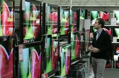 Мужчина рассматривает ТВ-панели в магазине бытовой электроники в Будапеште, 3 декабря 2008 года. Крупнейший российский ритейлер бытовой техники М.Видео, выстраивающий новую модель бизнеса, готов к проведению SPO в РФ и ждет подходящей рыночной конъюнктуры. REUTERS/Karoly Arvai