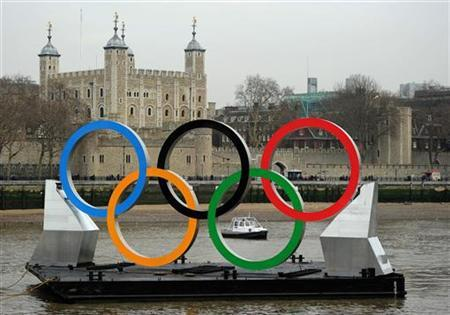Olympic rings, mounted on a barge, pass the Tower of London as they move east along the Thames river in London February 28, 2012. REUTERS/Ki Price/Files