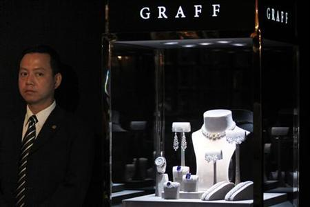 A suited bodyguard stands next to a jewellery display window during the Graff Diamonds IPO roadshow in Hong Kong May 21, 2012. REUTERS/Tyrone Siu