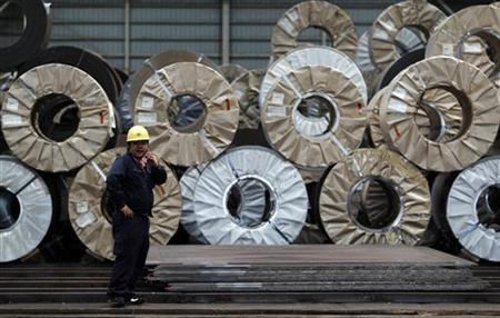 A worker uses a mobile phone in front of steel coils and steel sheets at a distribution warehouse in Urayasu, east of Tokyo April 19, 2012. REUTERS/Toru Hanai