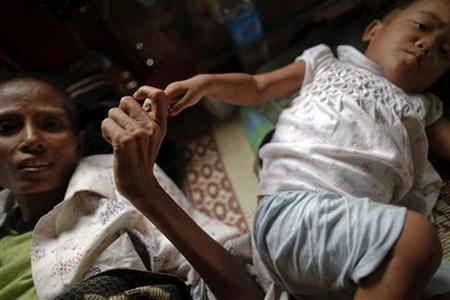 Ma Jam, a 42 year-old AIDS patient hold hands with 2 year-old HIV positive Kanama at the HIV/AIDS hospice founded by a member of the National League for Democracy (NLD) party in the suburbs of Yangon May 26, 2012. REUTERS/Damir Sagolj