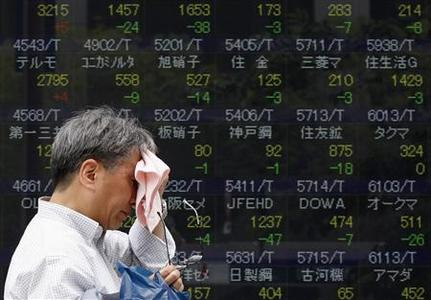A man wipes his face as he passes an electronic board displaying share prices outside a brokerage in Tokyo May 31, 2012. Asian shares, the euro and oil prices fell on Thursday as surging borrowing costs in troubled Spain heightened fears that more countries in the euro zone will be hit hard by the region's debt crisis. REUTERS-Yuriko Nakao