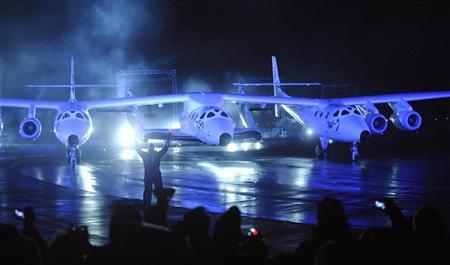 Virgin Galactic's SpaceShipTwo (C), which is carried by a twin-hulled aircraft named Eve, is unveiled in Mojave, California December 7, 2009. REUTERS/Phil McCarten
