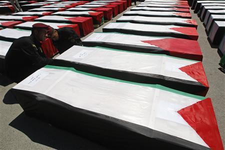 Members of the Palestinian security force adjust the flag covering a coffin containing the remains of the body of one of dozens of Palestinian militants, in the West Bank city of Ramallah May 31, 2012. REUTERS/Mohamad Torokman