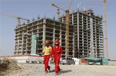 Workers walk in front of a multi-story commercial building under construction on the outskirts of the western Indian city of Ahmedabad May 31, 2012. REUTERS/Amit Dave