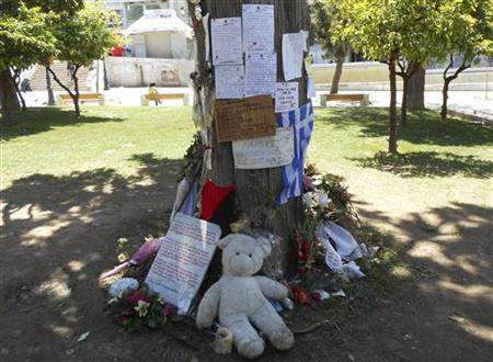 Flowers, toys and notes are seen at the site where pharmacist Dimitris Christoulas shot himself in the head because of poverty brought on by the crisis that has put millions out of work, in Athens' Syntagma square April 27, 2012. REUTERS/Erik Kirschbaum