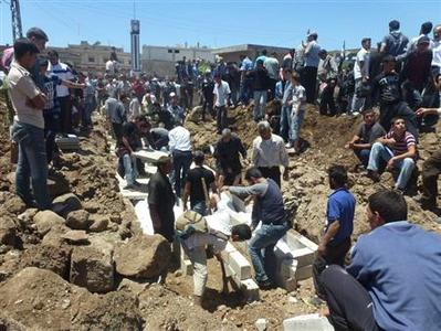People gather at a mass burial for the victims purportedly killed during an artillery barrage from Syrian forces in Houla in this handout image dated May 26, 2012. U.N. observers in Syria have confirmed that artillery and tank shells were fired at a residential area of Houla, Syria, where at least 108 people, including many children, were killed, the U.N. chief said on Sunday in a letter to the Security Council. REUTERS/Shaam News Network/Handout