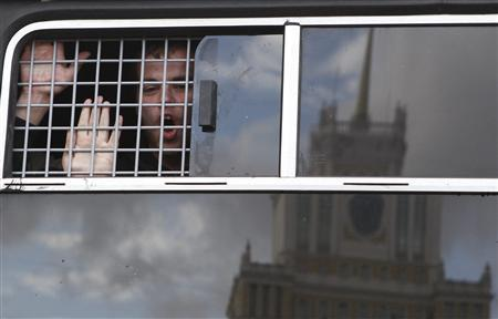 An opposition activist reacts inside a police bus after being detained during a protest rally to defend Article 31 of the Russian constitution, which guarantees the right of assembly, in Moscow May 31, 2012. REUTERS/Maxim Shemetov