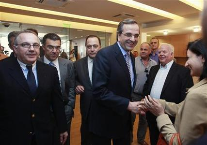Conservative New Democracy party leader Antonis Samaras (C) is greeted by a supporter as he arrives at the Athens Chamber of Commerce and Industry May 31, 2012. Greece's pro-bailout New Democracy (ND) party is ahead of the anti-bailout SYRIZA party in the run-up to a June 17 parliamentary election that may decide whether the debt-laden country remains in the euro, two polls showed on Thursday. REUTERS/John Kolesidis