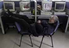 An investor sleeps on chairs next to computers showing stock information at a brokerage house in Wuhan, Hubei province in this February 20, 2012 file photo. China's official purchasing managers' index fell more than expected to 50.4 in May, the weakest reading this year and down from April's 13-month high, in the latest sign that output in the world's second-biggest economy is cooling. REUTERS/Stringer/Files