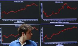 Мужчина на фоне экранов с рыночными котировками в фойе Афинской фондовой биржи 28 мая 2012 года. REUTERS/John Kolesidis