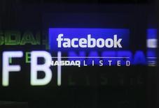 Логотип Facebook на экране на бирже Nasdaq Marketsite в Нью-Йорке, 18 мая 2012 года. Котировки Facebook Inc отскочили в четверг с рекордных минимумов, закрывшись в плюсе, благодаря общему росту рынка США и повышению оценки со стороны одной из брокерских контор. REUTERS/Shannon Stapleton
