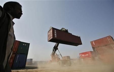 A worker prepares to stack a container at Thar Dry Port in Sanand in Gujarat February 1, 2011. REUTERS/Amit Dave/Files