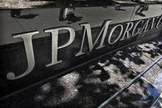 Commuters are reflected in stone as they walk past the JP Morgan headquarters in New York, May 17, 2012. REUTERS/Eduardo Munoz