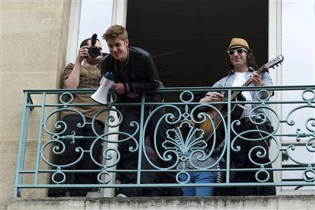 Canadian singer Justin Bieber (C) holds a megaphone as he looks down at fans from a balcony of his record label where he sang a musical set in Paris June 1, 2012. REUTERS/Julien Muguet