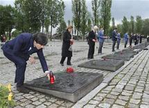 O técnico da seleção da Alemanha, Joachim Lowe (esquerda) planta uma vela à memória das vítimas do passado campo de concentração nazista em Auschwitz, 1º de junho de 2012. REUTERS/Markus Gilliar/Pool